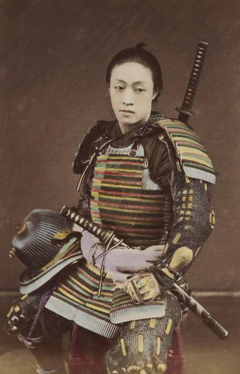 Hand-colored photo-portrait of a man in samurai armor.  Circa 1876, Japan.  Photographer Kozaburo Tamamura.