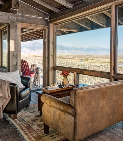 Simple, rustic mountain cabin decor - Floor-to-ceiling windows frame mountains in every direction, and squared, rather than rounded, logs create clean-lined walls.