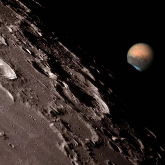 Изображение Марса, скользящего вдоль темного края Луны, получено во время экспедиции, организованной Обсерваторией Clay Center в Бонита Спрингс (Bonita Springs) во Флориде. Чтобы получить это изображение, были обработаны цифровым способом фотографии, сделанные с помощью телескопа. На переднем плане мы видим Луну, покрытую кратерами. Кажется, что яркий Марс находится от нее в угрожающей близости.