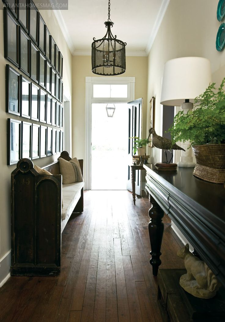 wide plank flooring, old church pew, gallery wall, light cream walls, long, black console & chandelier make this home say come on in!