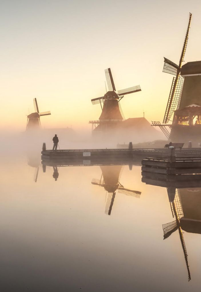 The historic windmills of Zaanse Schans, Zaanstad, Netherlands, in morning fog.