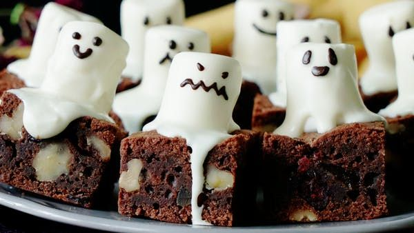 Recipe with video instructions: More treat than trick, these ghostly brownies will get you right in the Halloween spirit. Ingredients: 6 ounces dark chocolate, chopped, 1/2 cup butter, room temperature, 2 eggs, 1/2 cup sugar, Pinch of salt, 1/3 cup flour, 1/2 cup walnuts, chopped and toasted, 1/4 cup dried fruit, Decoration:, 12 marshmallows, White chocolate, melted, Chocolate writing pen
