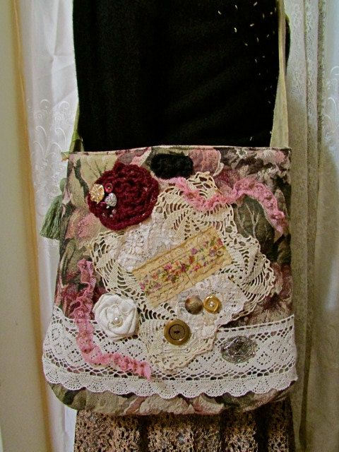 This upcycled fabric bag is handmade with thick tapestry fabric. The front is embellished with beads, buttons, wide cotton lace, a vintage crocheted