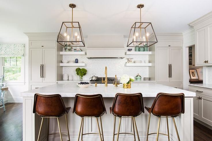 Four Global Home Stitched Leather Bar Stools sit in front of a light gray wainscoted center island topped with a honed carrera marble countertop lit by two filament light pendants.