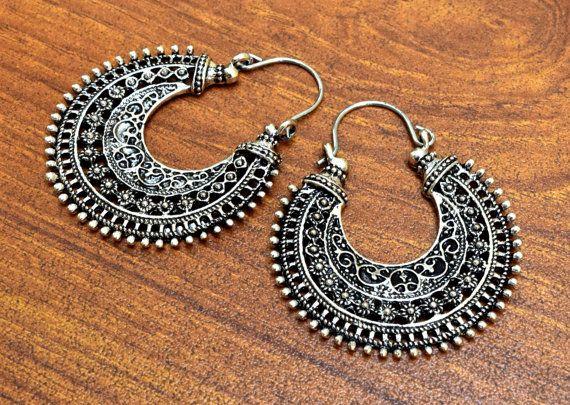 Orecchini a cerchio ornato tipico disegno indiano in colore argento. Questi orecchini di fusione forma di mezzaluna sono solitamente disponibili