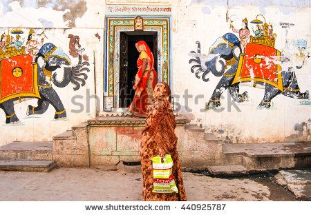 Bundi, Rajasthan, India. March 5, 2008. Street scene. Unidentified Indian women in bright clothes on the street. The walls of the house are decorated with traditional Rajasthani painting. - stock photo