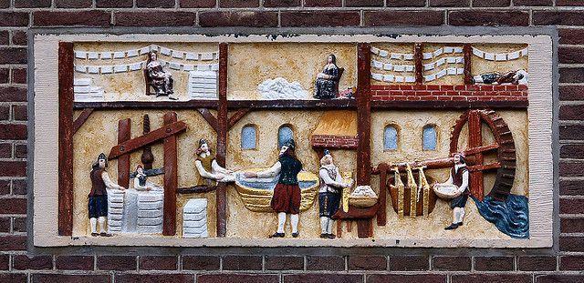 Het proces van het papier maken op een gevelsteen aan de Herengracht in Amsterdam