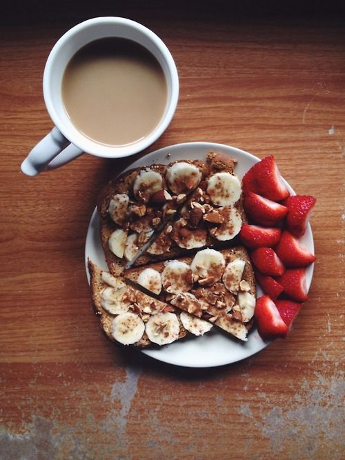 Whole grain toast with peanut butter and banana, topped with crushed almonds and cinnamon. Strawberries and coffee on the side.