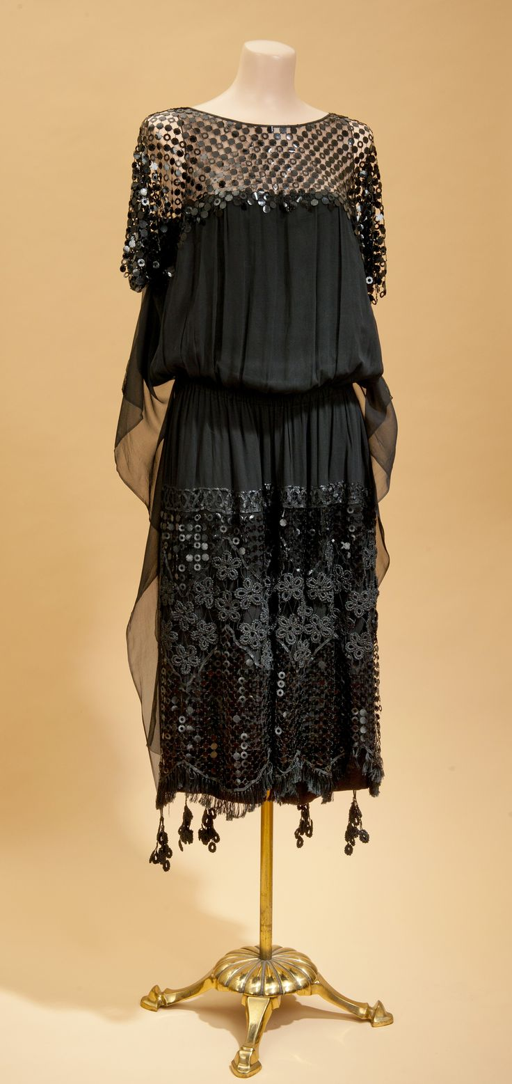 Early '20s dress with unusual sequin mesh and crocheted cord decoration. Long streamers with crocheted tassels hang from the shoulders and sheer panels hang from the sides in undulating curves.