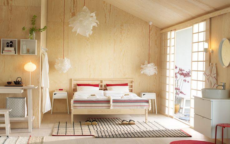 무가공 소나무 소재의 2인용 침대와 화이트 침대협탁, 레드/화이트 침구로 꾸민 중간 크기의 침실