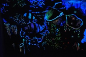 A black light only close up of the coral in an underwater mural created with Modern Masters Wildfire Luminescent Paints. By AG Murals