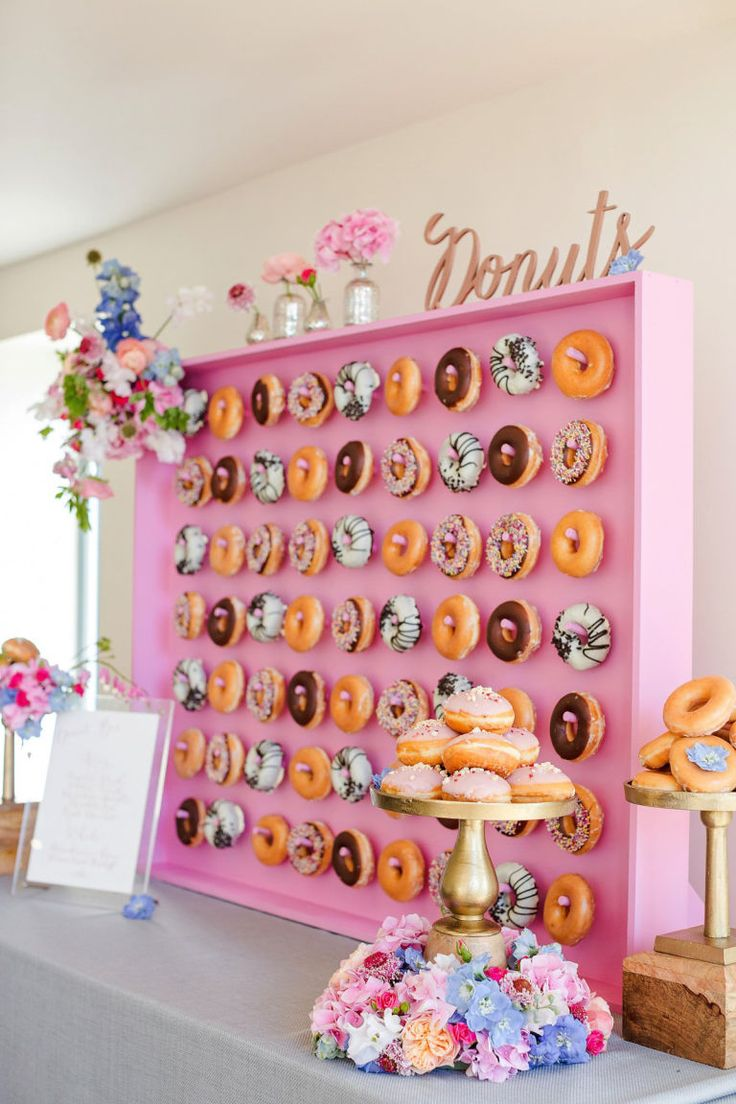 Flower walls might have been the hottest thing to have at your wedding in 2014, but there's something just as beautiful — but way more delicious — blowing up right now. Meet the donut wall: They've been popping up in our Instagram feeds over the last few months and we couldn't be happier about it. But the best part is, donut walls are adaptable for any style of wedding — or any party, really. For example, they can be super romantic. Click through for more donut wall inspiration.