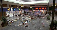 Film screenshot showing a police car driving through a shopping mall: Scattered items are present on the floor and people are running away from the vehicle. Stores visible in the mall include Toys 'R' Us and Jewel.