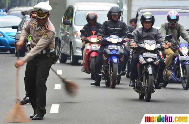 Polisi membersihkan jalan dari tebaran ranjau paku dekat Istana Merdeka sepanjang Jalan Medan Merdeka Utara, Jakarta, Selasa (15/5).