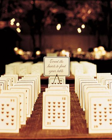 The number of hears on tented playing cards designates table assignments. The guests' names are on the other side.