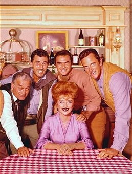 Promotional portrait of the cast of the American television series 'Gunsmoke,' 1964. Seated is American actress Amanda Blake (1929 - 1989) (as Kitty Russell); behind her, from left, American actors Milburn Stone (1904 - 1980) (as Dr. Galen Adams), Ken Curtis (1916 - 1991) (as U.S. Deputy Marshal Festus Haggen), Burt Reynolds (as Quint Asper), and James Arness (as U. S. Marshal Matt Dillon).