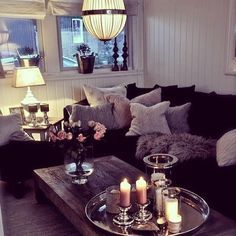 This cosy living room area includes cushions and candles - perfect for creating a romantic vibe. Find more black and silver living room ideas here: https://nyde.co.uk/blog/black-and-silver-living-room-ideas/