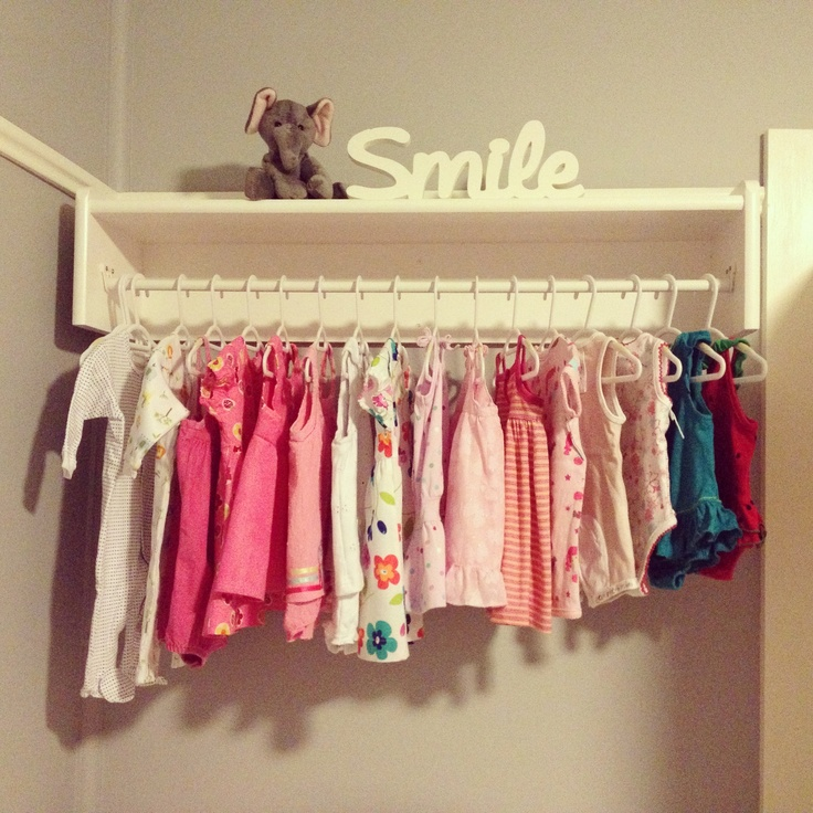 Part of old bookshelf converted into a mounted shelf and clothes rack for our nursery.