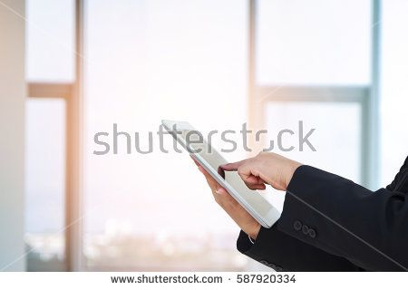 business woman use a pc tablet with blurred image of glass of office.