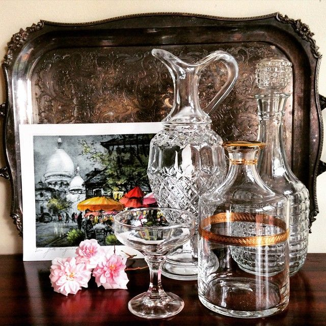 Style a bar area or create a DIY cocktail tray with an eclectic collection of vintage crystal carafes & bottles. Paired with an antique silver tray & painting of Paris this is the perfect way to add some vintage inspiration to your wedding decor! #love #crystal #glass #bar #cocktail #champagne #coupe #bottle #carafe #vintage #vintagehome #vintageglass #paris #flower #flowers #rose #antique #silver #tray #wedding #vintagewedding #weddingdecor