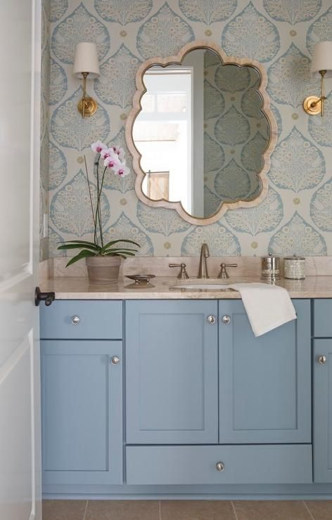 Beautiful blue powder room features a blue shaker washstand topped with cream stone fitted with a round sink and satin nickel faucet placed under a cream bone inlay scalloped mirror lining a wall clad in gold and blue lotus wallpaper, Galbraith and Paul Lotus Wallpaper, illuminated by Thomas O'Brien Bryant Sconces.