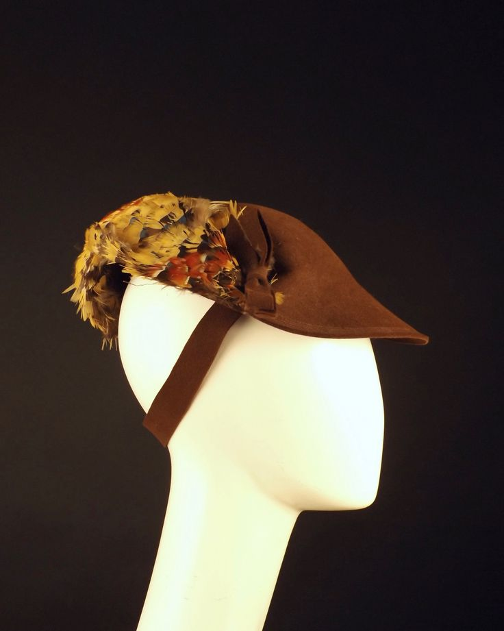 Late 1930s hat in brown wool felt. The hat is a round, sculpted hat with pheasant feathers around the back side. Back strap in felt helps counterbalance the tilt of the hat is to be worn. Condition: S