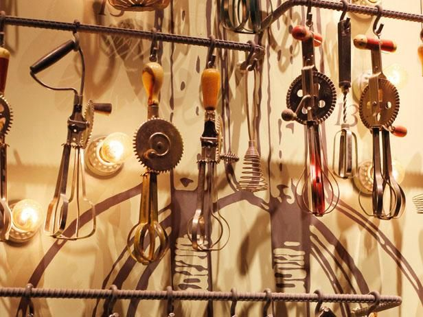 Guy Fieri's NYC Restaurant : A wall of vintage egg beaters.