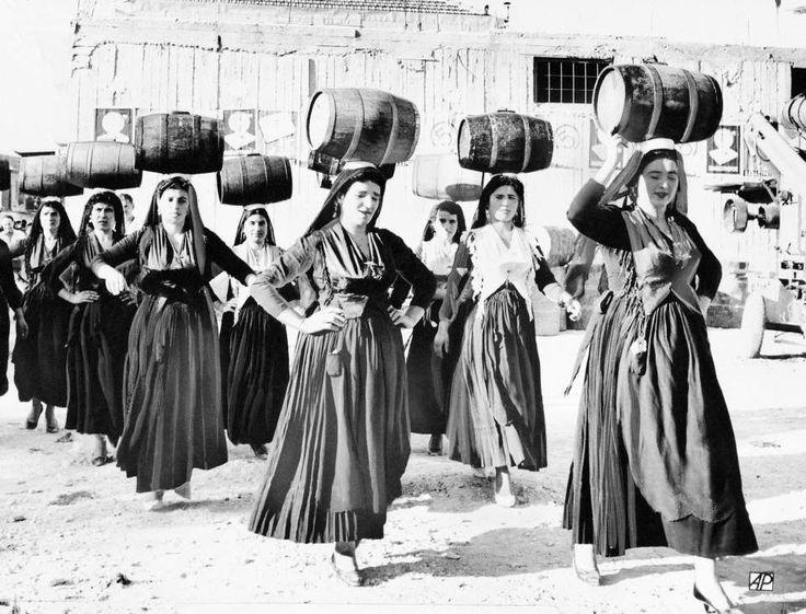 Γυναίκες με παραδοσιακές φορεσιές στη Λευκάδα παρουσιάζουν έναν παραδοσιακό χορό στο Διεθνές Φεστιβάλ Λαογραφίας που διεξάγεται στο νησί, το 1963. Ο συγκεκριμένος χορός παραδοσιακά λαμβάνει χώρα πριν από τη συγκομιδή και το πάτημα των σταφυλιών, όπως χαρακτηριστικά υποδεικνύουν τα βαρέλια που οι χορεύτριες ισορροπούν στα κεφάλια τους. (ΑP Photo)