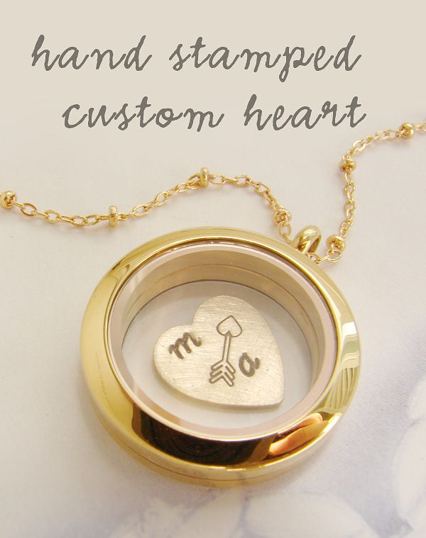 A small glass encasement for the brass heart inside, this locket holds a small charm stamped with two initials and an arrow. The round locket allows the heart to float freely inside and can be opened to add other small charms, glitter, beads or even bits of flora. Choose from two different metal finishes, for a shiny bezel in gold or silver.