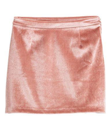 Oudroze. Een korte rok van elastisch fluweel met een blinde ritssluiting aan de zijkant. Ongevoerd.