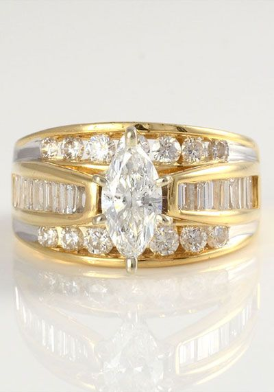 Estate yellow gold marquise diamond ring. The ring is set in 14 karat yellow gold with a 0.75 carat center marquise diamond VS1 clarity H color enhanced with 18 baguettes and 14 round diamonds at 1.40 carat total weight VS-SI clarity G-I color, 2.15 carat total weight all diamonds.