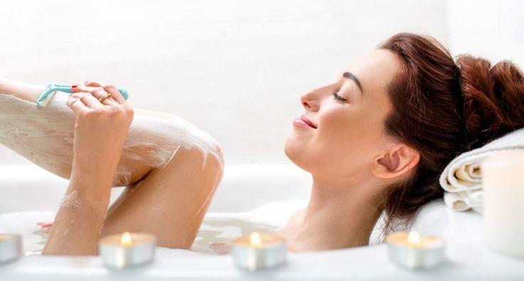 kvinde i bad mens hun barberer sine ben med en skraber, stearinlys i forgrunden