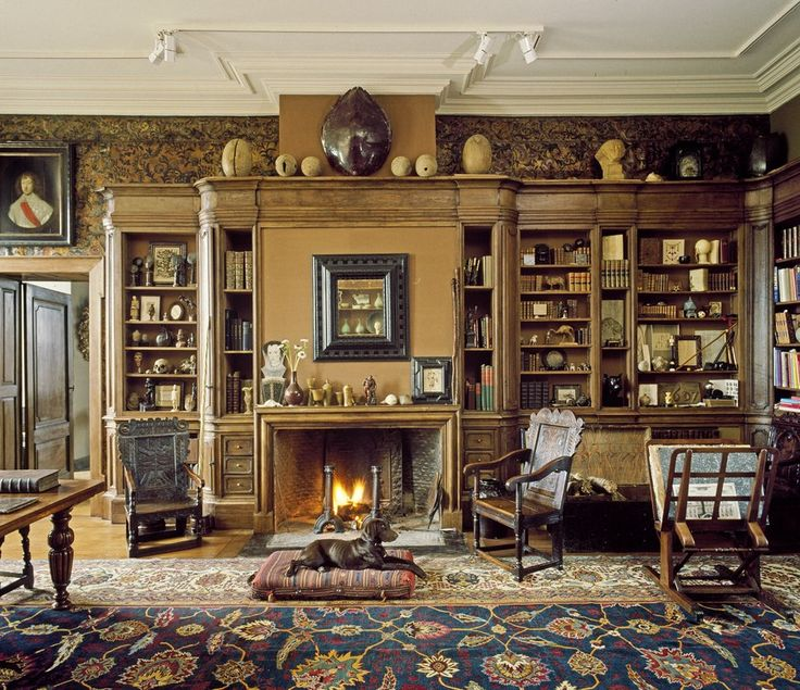 In the library at his castle in Belgium, featured in October 1986, Axel Vervoordt created a warm and layered space with beloved antiques and a vibrant Agra carpet. The walls are covered in cordovan leather, and his hunting dog, Juno, rests in front of the fire.