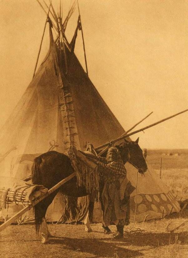 Transporting the ceremonial bag and tipi-cover of a Blackfoot society, Edward Curtis