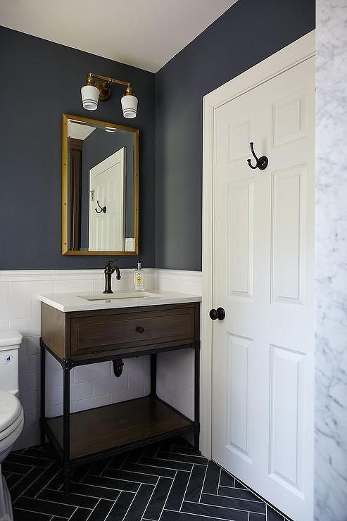 Blue And Gray Kid S Bathroom Features Upper Walls Painted Dark Blue And Lower Walls Clad In Herringbone Tile Floorstiled