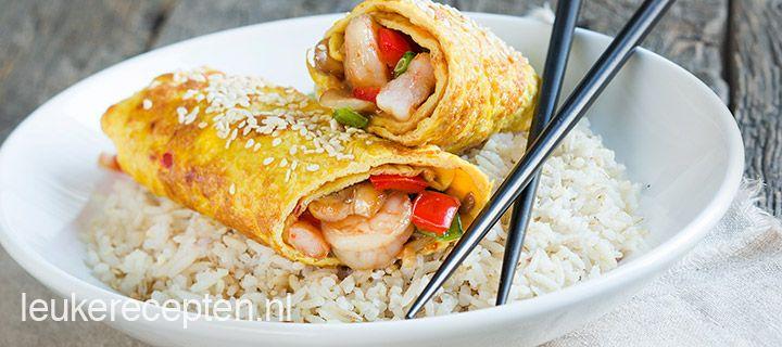 Oosterse roerbak met groente, garnalen en teriyaki verpakt ik een omeletrol met sesamzaadjes.