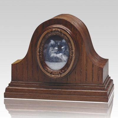 The Tambour Pet Cremation Urn modeled after a traditional old-fashioned mantel clock with a tambour frame to bring a bit of Early American elegance to your memories of your pet. The piece is crafted of cultured material to give a natural wood grain appearance.