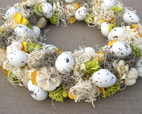 Easter wreath, made with a combination of dried natural materials, plastic eggs and paper and fabric flowers.