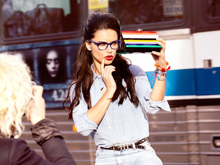 Adriana Lima stops for a quick touch-up between shots behind the scenes of our Rainbow shoot.