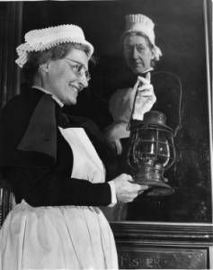 1949 - Old nurse uniforms :: George D. McDowell Philadelphia Evening Bulletin Photographs - Miss Ernestine Kittl D' Estel, modeling a nurse's costume worn in 1883. A portrait of Alice Fisher, chief nurse of the Philadelphia General Hospital in 1883 is wearing identical uniform. The lamp was used for lighting in hospitals in that period.