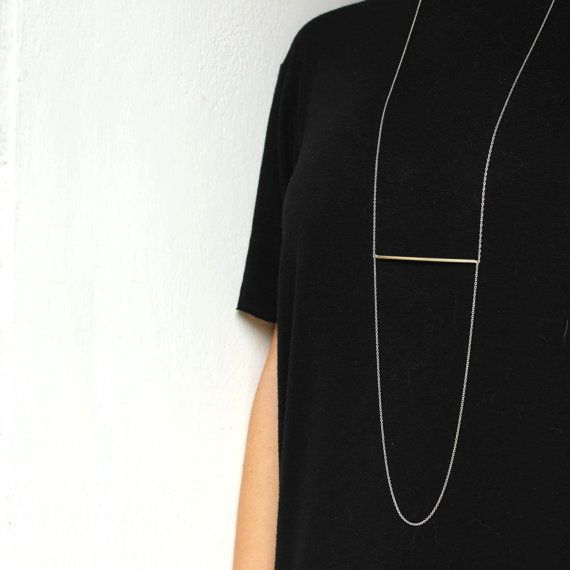 This is a long super tiny necklace with a sterling silver chain and a tube in the middle that creates a geometric look. Very simple and chic.