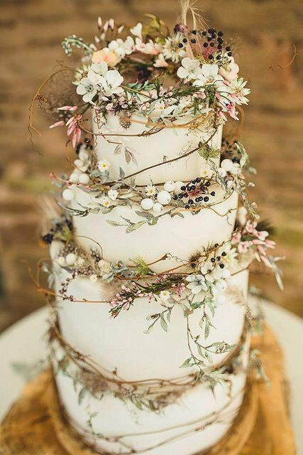 Simple white wedding cake with fresh flowers and greenery topper and cascading v…