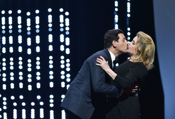 Catherine Deneuve Photos - French actress Catherine Deneuve (R)embraces French actor and Master of Ceremony Laurent Lafitte on stage on May 11, 2016 during the opening ceremony for the 69th Cannes Film Festival, southern France. / AFP / ALBERTO PIZZOLI - 'Cafe Society' & Opening Gala - Red Carpet Arrivals - The 69th Annual Cannes Film Festival