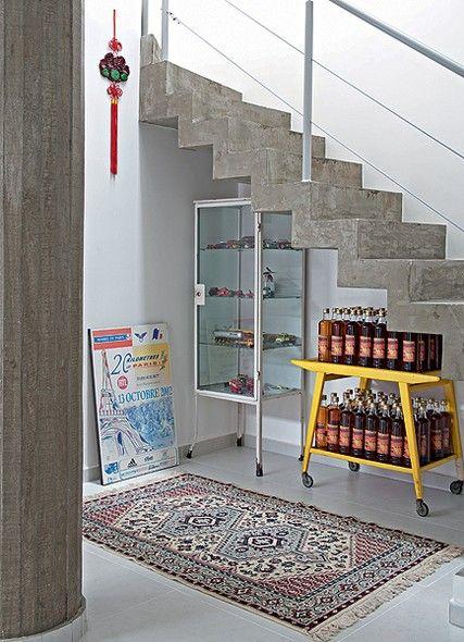 O espaço embaixo da escada de concreto expõe o armário de farmácia com miniaturas de carros e o carrinho de chá com as garrafas de cachaça envelhecida na cobertura da casa. O cartaz é do morador maratonista. Projeto do escritório Casa 41 Arquitetura