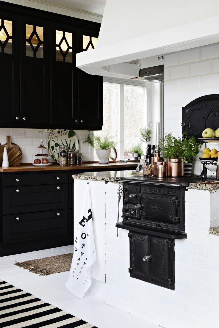 Mörkt kök känns så rätt och det ljusas upp av vit vedugn, vita kakel och varma färger i bänk och inredning.