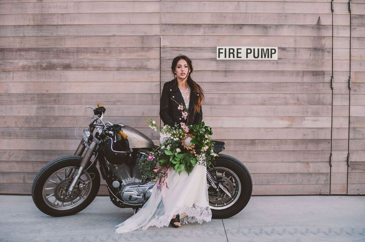 Edgy + modern bride wearing a leather jacket posing with a motorcycle