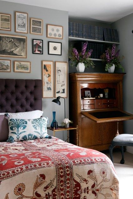 a personal collection of art hangs in a worldly bedroom. patterned bedspread, secretary desk, tufted headboard