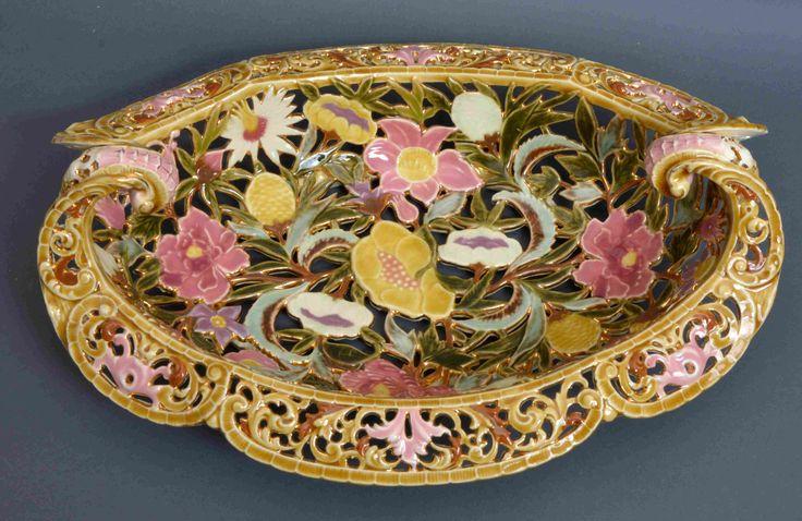 Zsolnay DÍSZTÁL porcelánfajansz, áttört ovális karéjos forma befelé hajló fülekkel, színesen festett virágmintás díszítéssel. Jelzett: máz alatt barnával, öttorony és benyomott MADE IN AUSTRIA-HUNGARIA ZSOLNAY PÉCS. Fazonszám: 4007 1800-as évek vége. Méret: 14,5x40,5x30 cm 16/204