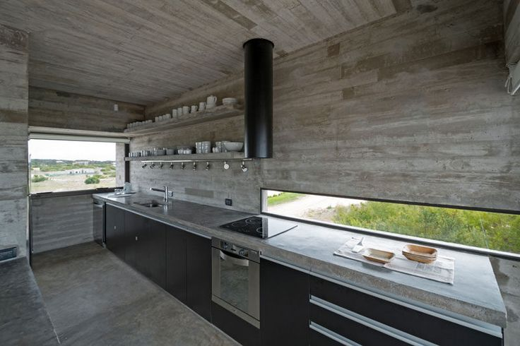 """Horizontal """"letterbox"""" style windows are a design detail I love. These long, thin, horizontal windows are perfect for bringing in light without sacrificing privacy,  This skinny letterbox window brightens up the dark black cabinets and concrete used throughout this kitchen, and looks out over the nearby golf course."""