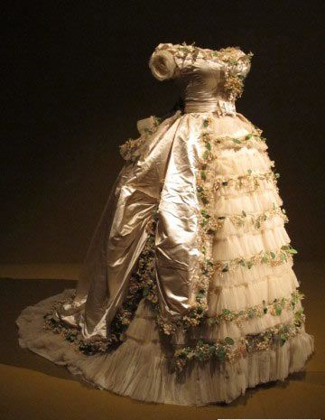 1869 wedding gown of Elisabeth of Wied, Queen Consort of Romania. The dress is made of silk satin, silk tulle with cotton and paper faux flowers. Held at FIDM.